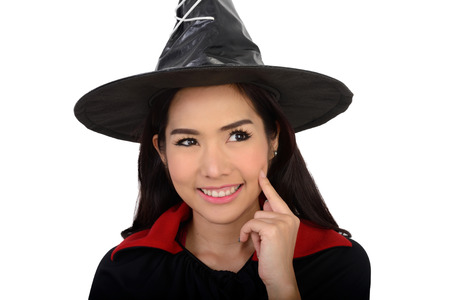 to tease: Pretty girl in witch suit smiling and put her finger on cheek on white background. Stock Photo