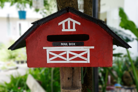 Red handmade mailbox hang on tree in front of house. Stock Photo