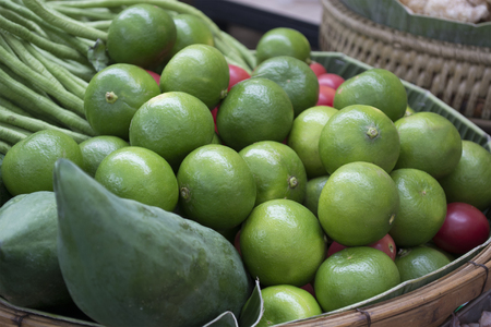 enhances: Green lime is a condiment that enhances the taste for Asian food sold at rural markets. Stock Photo