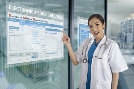 Female doctor introduced electronic medical record system show on transparent display on glass windows.