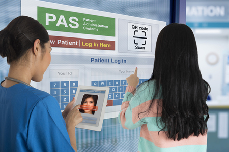 Female Patient using self registration system to check in while doctor find her medical record by digital tablet.
