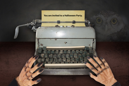 Devil's hand typing invitations for Halloween with old typewriter. 写真素材