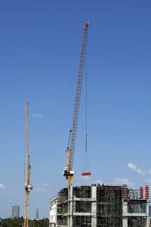 Crane lifting material for building construction on bright blue sky.