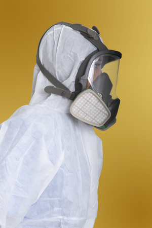 Side view of female worker in air pollution protection suit on yellow background.