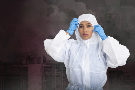Female worker wearing pollution protection suit on dark background.