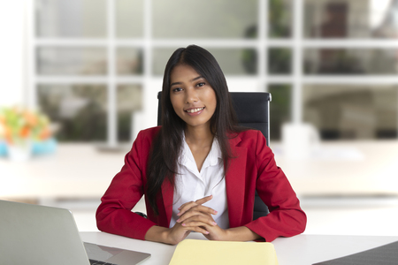 Nice and smiling business woman wearing red suit sitting in office. 스톡 콘텐츠