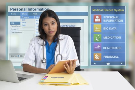 Female doctor sitting in office with electronic medical record screen on background. 스톡 콘텐츠