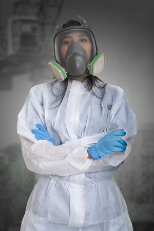 Female worker in dust protection suit standing with her arm crossed.