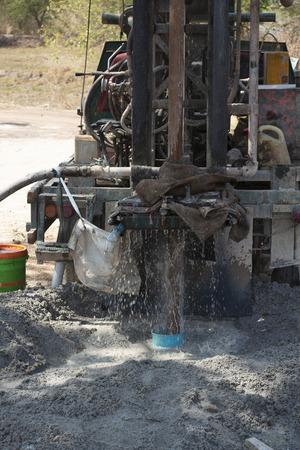 Close-up photo of machine drilling into ground while found underground water.