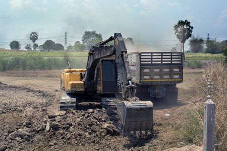 Backhoe digging to fill soil in dump truck at construction site. Banco de Imagens