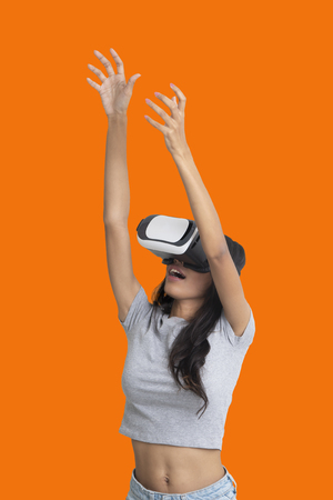 Girl put her hands up while playing multimedia game with virtual reality glasses on orange background. Archivio Fotografico