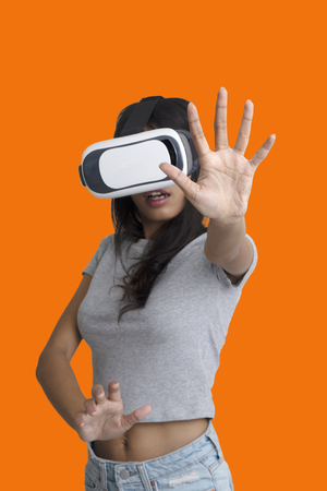 Girl put her hands to catch something while playing multimedia game with virtual reality glasses on orange background.
