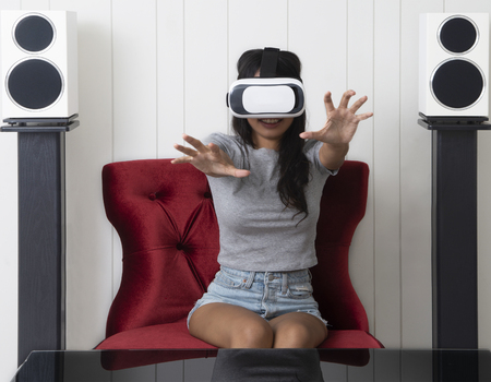 Girl look so happy while using multimedia technology with virtual reality glasses.
