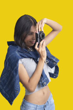 Girl holding compact camera in hands and take photo on yellow background.