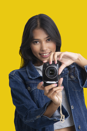 Girl taking photograph by compact camera in hands on yelloww background.
