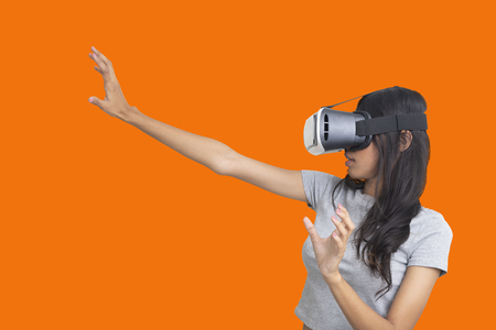 Side view photo of girl try to catch sometiong while playing multimedia game with virtual reality glasses on orange background.