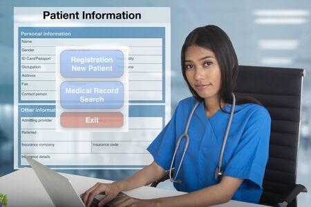 Ärztin, die an Notebook-Computer mit Krankenakten- und Registrierungsformularbildschirm im Hintergrund arbeitet. Standard-Bild
