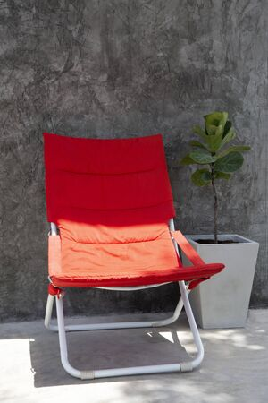 Red beach chair on outdoor terrace in contrast of color and light.