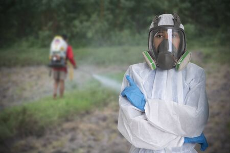 Female worker in hazard protective suit with farmers spray pesticides without protection on background.
