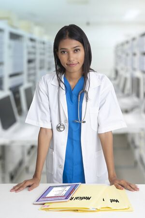 Female doctor standing with medical record folder and tablet on desk. 스톡 콘텐츠