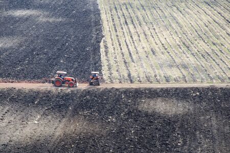 Two tractors working on burned farmland.