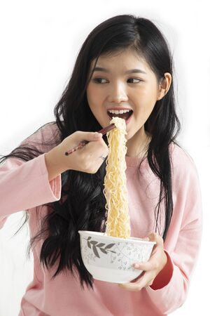Girl enjoy eating while using chopsticks to hold instant noodles into her mouth on white background.
