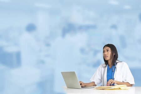 Female doctor working infront of blur blue background of medical laboratory.