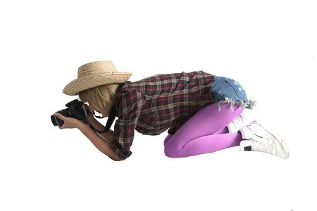 Studio shot of female photographer squat on the ground to take close up photo on white background. 스톡 콘텐츠