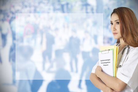 Female doctor standing in the side holding epidemiologic report in hands with blue background of crowd behind.