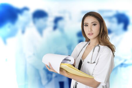 Female doctor holding medical report in hands with photo of medical staff on background. 스톡 콘텐츠