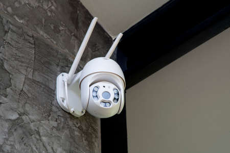 Round shape security camera hanging on wall to monitor movement around.