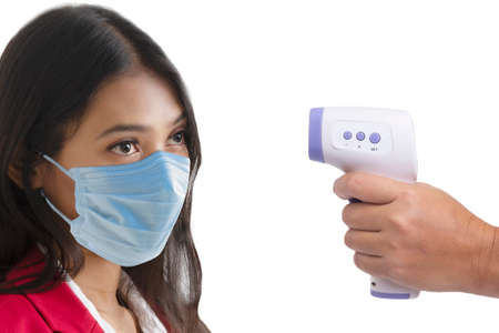 Side view photo of woman face who was being measured body temperature with electronic handheld thermometer.