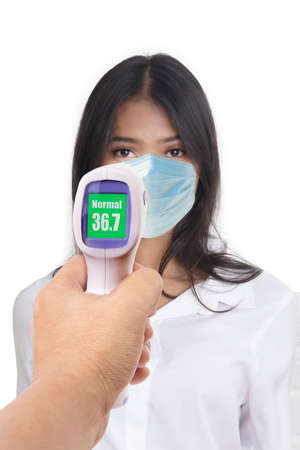 Front view photo of woman who was being measured body temperature with electronic handheld thermometer on white background.