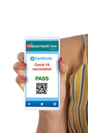 Covid-19 vaccineation certificate showing on smarthphone in woman hand on white
