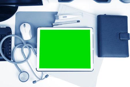 Digital tablet showing green screen on a doctor's desk.