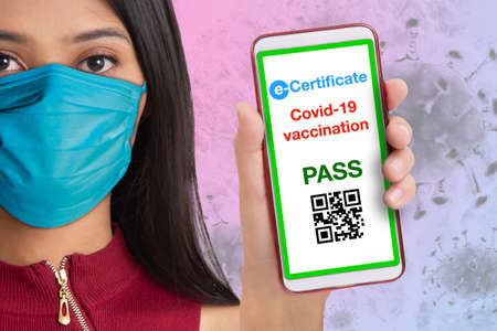 Woman wearing face mask showing electronic covid-19 vaccineation certificate on her smarthphone. Foto de archivo