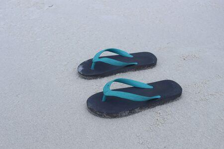 Flip flops on a sand beach