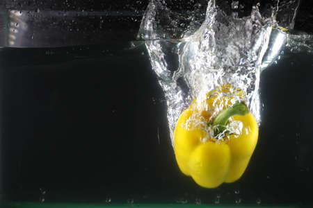 Yellow sweet pepper dropped into water and created a water splash