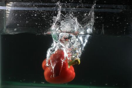 Red sweet pepper dropped into water and created a water splash