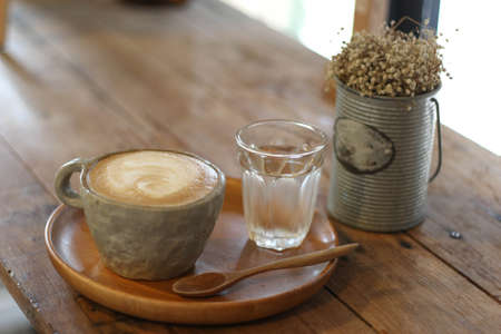 Hot latte with water, soft and blur background