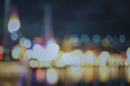 Blur the background of many buildings by the river at night with colorful lights in the beautiful city of Da Nang, Vietnam. There are many spherical bokeh and water reflections. Feeling fun and happy.