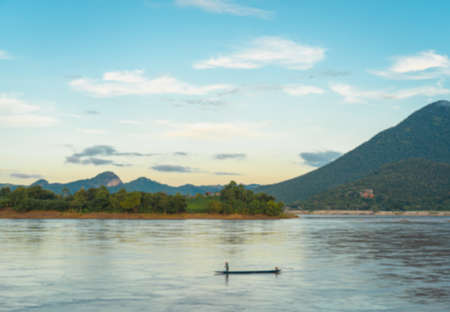 Blur background of a boat with fishermen standing and dragging his nets in Mekong River in evening. The backdrop is mountains and lush vegetation with cloudy blue sky. Feeling peaceful and freedom.