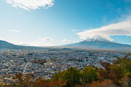 Cityscape views of the city near the volcano in the autumn from the Chureito Pagoda, Japan. There is Mount Fuji with snow on the top with a clear blue sky. There are colorful houses and buildings. Standard-Bild