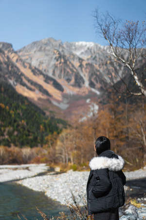 Photos from the side of an Asian woman standing by the river in Kamikochi, Japan. There are many colorful trees of autumn and the tops are covered with snow. The idea of traveling alone. Standard-Bild