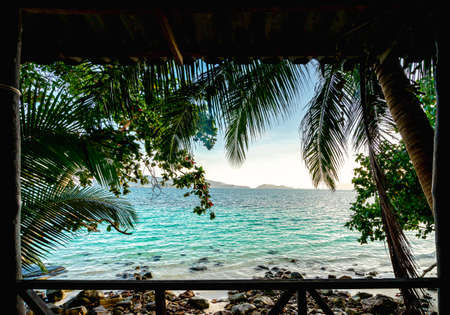 Front view on the wooden terrace in the morning is beautiful seascape. There have clear skies and many coconut trees. And Blue ocean, white sand beaches, and numerous rocks. Peaceful holiday concept.
