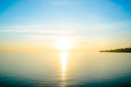 Front view in the indigo blue ocean in the morning, the sun was rising, reflections fell on the smooth calm surface with golden warm light.  The sky is clear and clean. Feeling refreshed and relaxed.