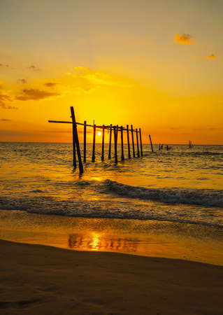 The view of the old wooden bridge decayed in the middle of the ocean in the evening. The sun is setting, making the sky a golden yellow. The waves hit the shore with orange light. There is copy space.