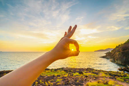 The image of a hand posed okay with the sun in the circle. The backdrop is the ocean in the evening, sunset, reflections fell on the calm surface with golden warm light. Feeling refreshed and relaxed. 免版税图像