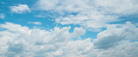 Background picture low angle of bright blue sky on a sunny day. There are fluffy white clouds and clear. Blue and white color contrast in soft tones. feeling fresh and relax. There is a copy space. 版權商用圖片