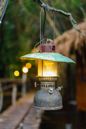 Close-up photo of an old lamp made of iron with a yellow light in the center hanging from a branch. Blurred background of forest, cabins, hallways, and bokeh. The idea for vintage wallpaper.